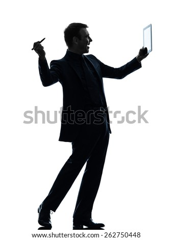 one  business man holding digital pen stylus tablet in silhouette on white background - stock photo