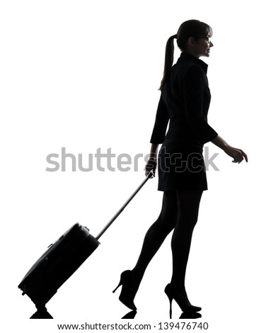 one business woman traveler walking suitacse  silhouette studio isolated on white background