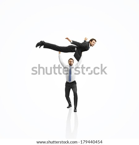 One businessman lifting the second one and helping him to fly. Team work concept. - stock photo