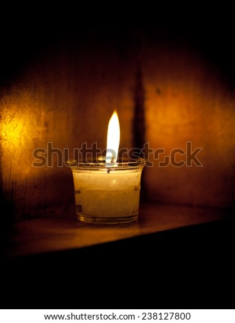 One candle flame at night closeup in dark box  - stock photo