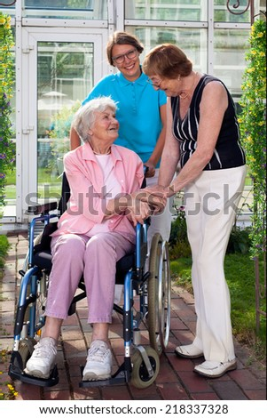 One Care Takers for Elderly Patient on Wheel Chair together with her friend in Outdoor Capture with Glass Building at Background. - stock photo