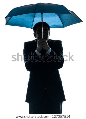 one caucasian anxious business man under umbrella  in silhouette studio isolated on white background - stock photo