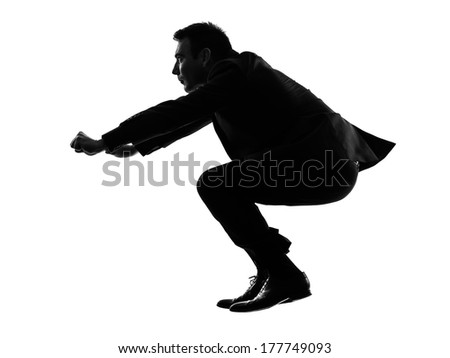 one caucasian business man driving imaginary motorcycle in silhouette on white background