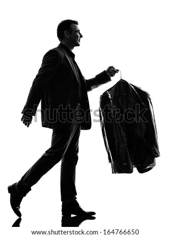 one caucasian business man holding dry clean clothes in silhouette  on white background - stock photo