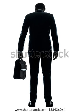 one caucasian business man sad standing rear view  in silhouette studio isolated on white background - stock photo