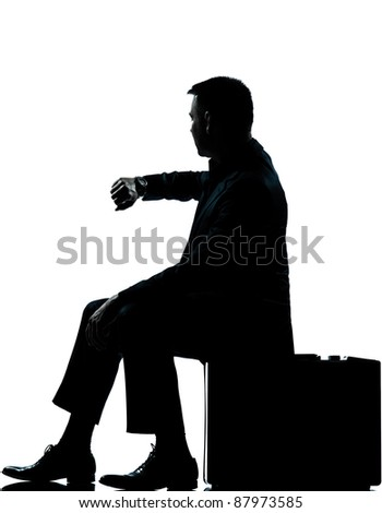 one caucasian business man sitting on suitcase checking time silhouette Full length in studio isolated on white background