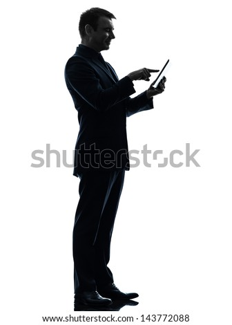 one caucasian business man touchscreen digital tablet   in silhouette on white background - stock photo