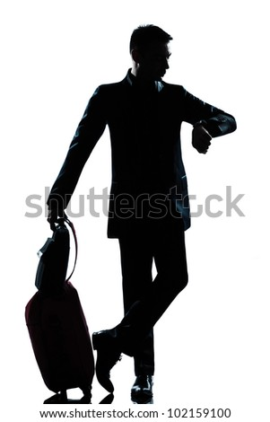 one caucasian  business traveler man checking the time full length silhouette in studio isolated on white background - stock photo