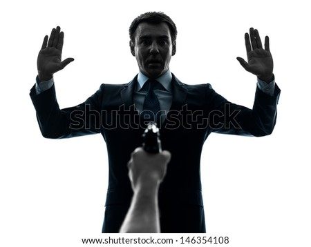 one caucasian businessman arms raised with gun pointing at him in silhouette studio isolated on white background - stock photo