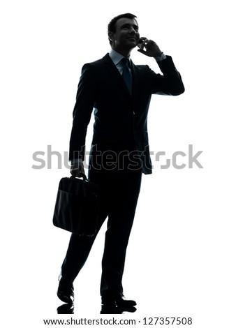 one caucasian businessman walking on the telephone in silhouette studio isolated on white background - stock photo