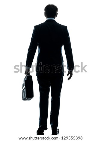 one caucasian businessman walking rear view in silhouette studio isolated on white background - stock photo