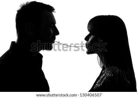 one caucasian couple man and woman eating the same spaghetti in studio silhouette isolated on white background