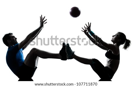 one caucasian couple man woman personal trainer coach exercising tossing fitness ball silhouette studio isolated on white background - stock photo