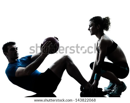 one caucasian couple man woman personal trainer coach exercising weights fitness ball silhouette studio isolated on white background - stock photo