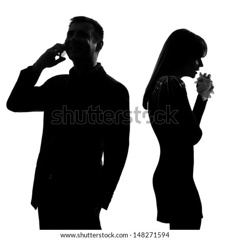 one caucasian couple standing back to back man on the phone  and woman crying in studio silhouette isolated on white background - stock photo