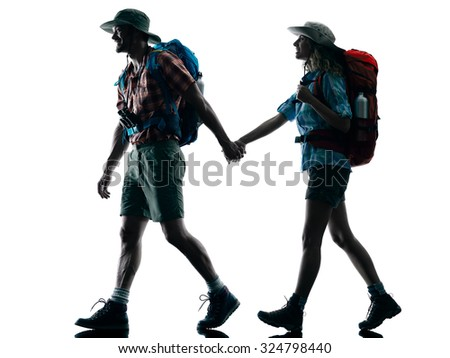one caucasian couple trekker trekking walking nature in silhouette isolated on white background - stock photo