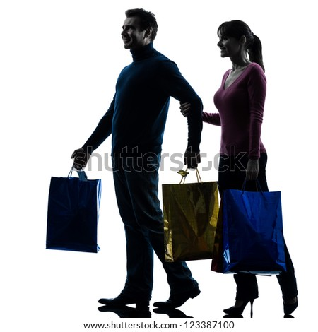 one caucasian couple woman man christmas present shopping  in silhouette studio isolated on white background - stock photo