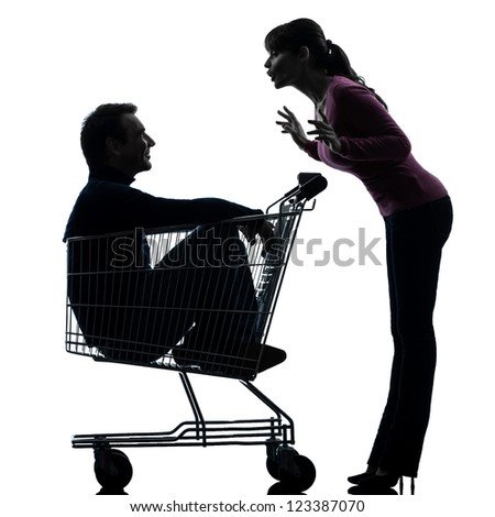 one caucasian couple woman  with man sitting in shopping cart   in silhouette studio isolated on white background - stock photo