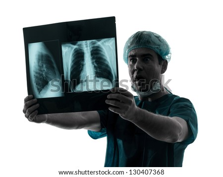 one caucasian man doctor surgeon radiologist medical surprised  examaning lung torso  x-ray image silhouette isolated on white background - stock photo