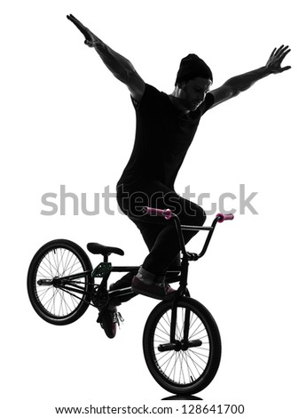 one caucasian man exercising bmx acrobatic figure in silhouette studio isolated on white background