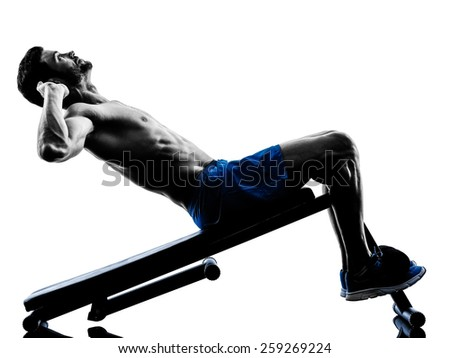 one caucasian man exercising fitness crunches crunches Bench Press exercises in studio silhouette isolated on white background - stock photo