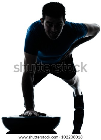 one caucasian man exercising push ups on bosu workout fitness in silhouette studio  isolated on white background - stock photo