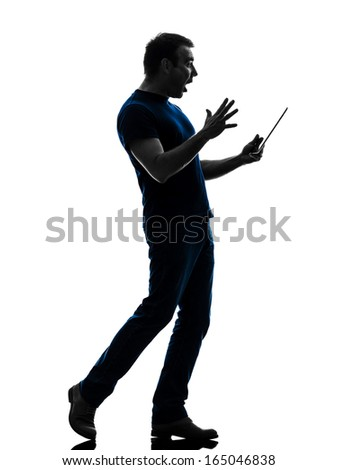 one caucasian man holding digital tablet surprised in silhouette on white background - stock photo