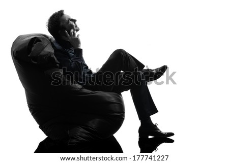 one caucasian man sitting on the telephone in silhouette studio isolated on white background