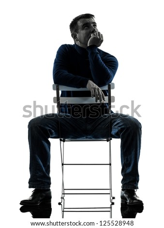 one caucasian man sitting  thinking pensive  full length in silhouette studio isolated on white background - stock photo