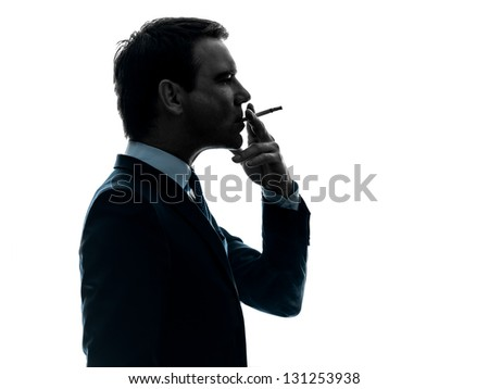 one caucasian man smoking cigarette  in silhouette studio isolated on white background - stock photo