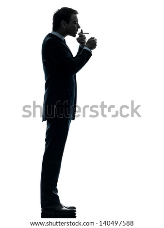 one caucasian man smoking cigarette  in silhouette studio isolated on white background