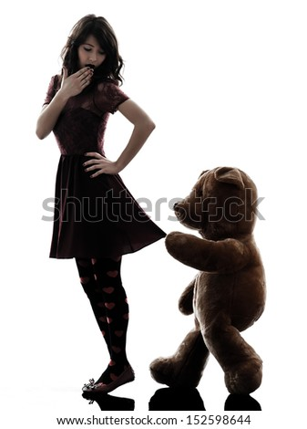 one caucasian strange young woman and vicious teddy bear  in silhouette white background - stock photo