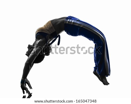 one caucasian woman capoeira dancer dancing backflip in silhouette studio on white background - stock photo