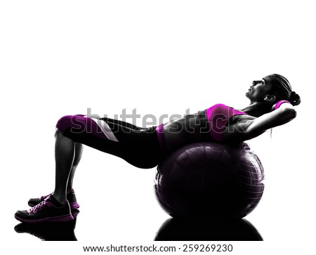 one caucasian woman exercising  fitness ball crunches  in studio silhouette isolated on white background - stock photo