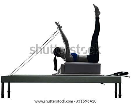 one caucasian woman exercising pilates reformer exercises fitness in silhouette isolated on white backgound - stock photo