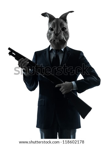 one causasian man rabbit mask hunting with shotgun portrait in silhouette studio isolated on white background