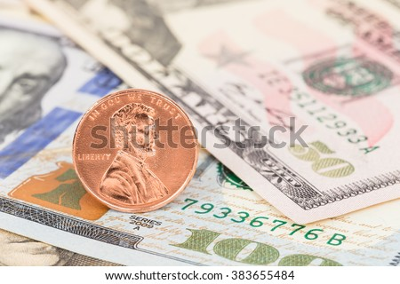 One cent coin stand on us dollar banknote money - stock photo
