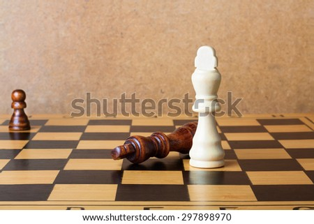 One chess king dominating another on the chessboard - stock photo