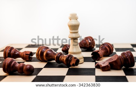 One chess piece standing after the fall of many others - stock photo
