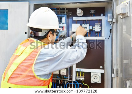 One chinese electrician builder at work with high voltage power electric line distribution fuseboard - stock photo
