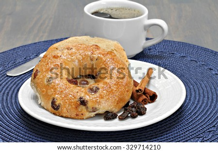 One cinnamon raisin bagel buttered and toasted with a side of coffee. - stock photo