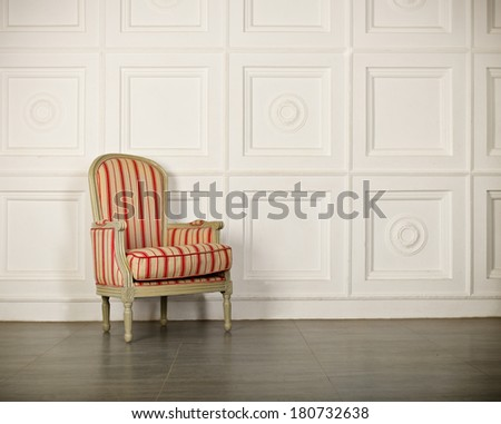 One classic armchair against a white wall and floor. Copy space - stock photo