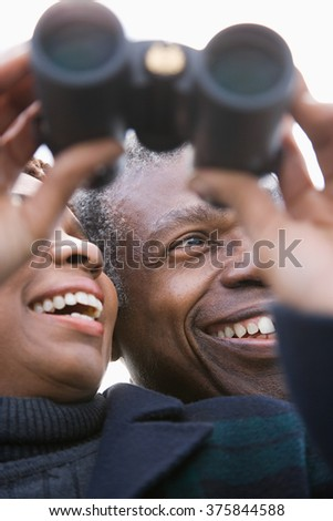 One couple looking through binoculars