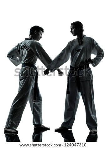 one couple man woman couple exercising karate taekwondo martial arts in silhouette studio isolated on white background - stock photo