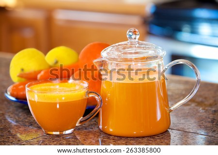 One cup of orange colored juice on kitchen counter with fruit and vegetables in background. Carrots, apples, lemons, oranges. - stock photo