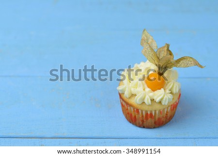 One cupcakes with cream cheese on a blue wooden background
