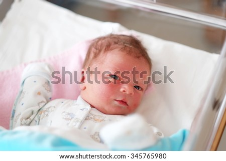One day old newborn baby in bed  - stock photo