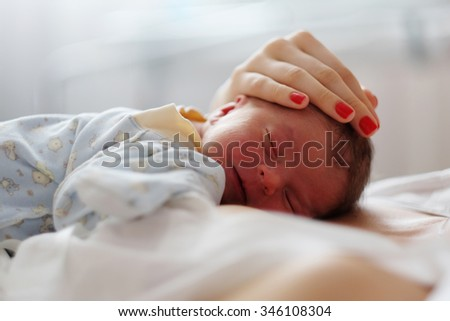 One day old newborn baby with his mother - stock photo