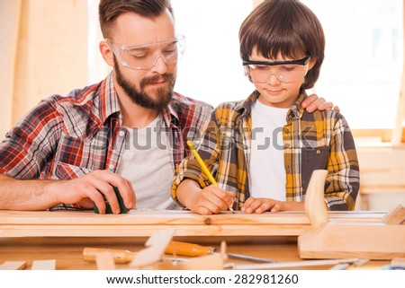 One day you will be a talented carpenter. Concentrated young male carpenter teaching his son to work with wood in his workshop - stock photo