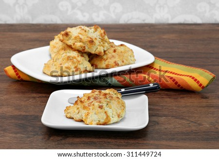 One delicious garlic cheese and cheddar biscuit on a plate with more biscuits behind.  Selective focus on front biscuit.  Copy space. - stock photo